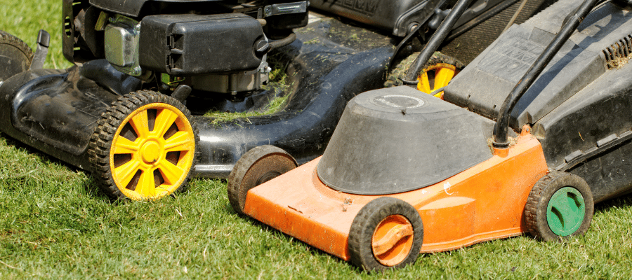 two gas powered lawnmowers on lawn