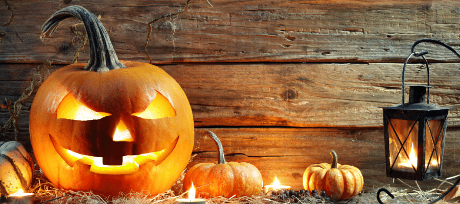 Jack-o-lantern with candles in front of wood background