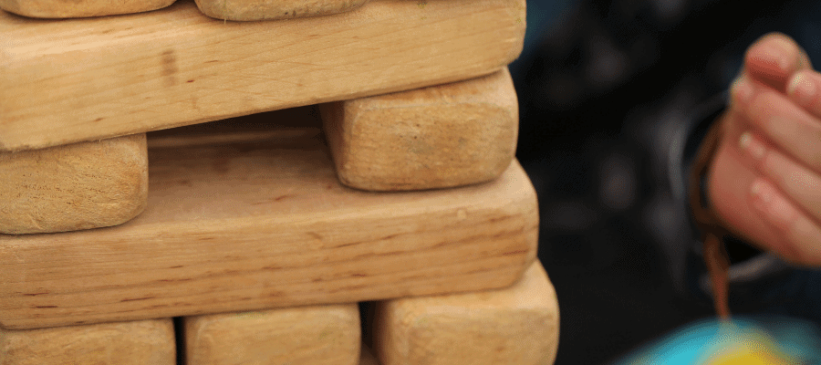 Large wooden Jenga tower with middle piece missing.