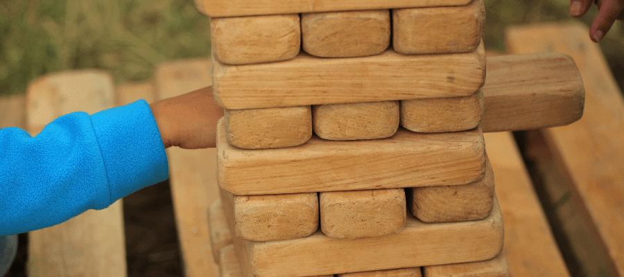 Hand pushing out large wooden Jenga piece.
