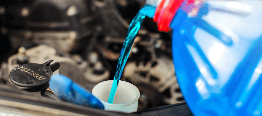 Blue antifreeze being poured in engine