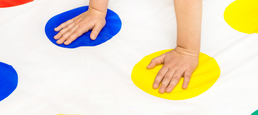 one hand on blue circle, another on a yellow circle playing Twister