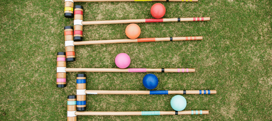 Six different colored croquet mallets with matching croquet balls