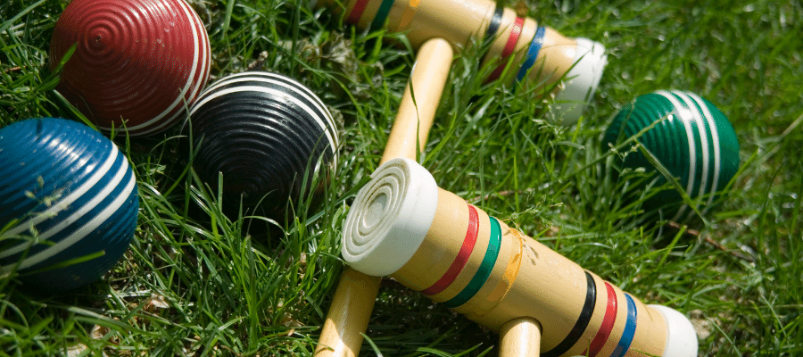 Two croquet mallets with four croquet balls on green grass