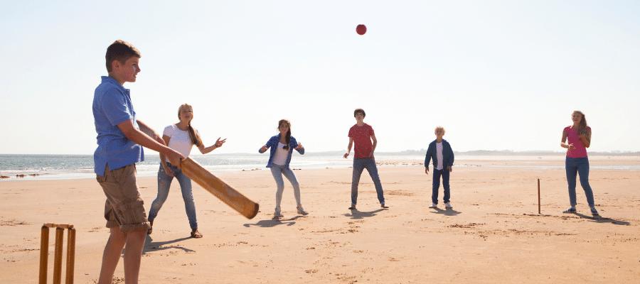 Six teens playing cricket on a beach