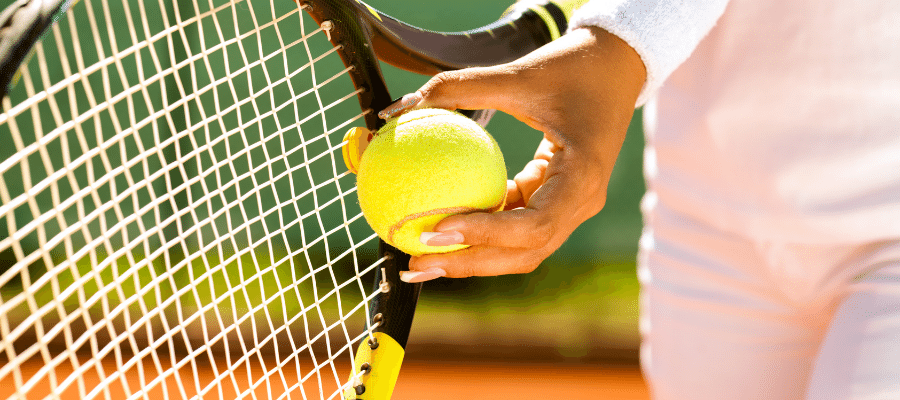 Hand holding tennis ball and racket
