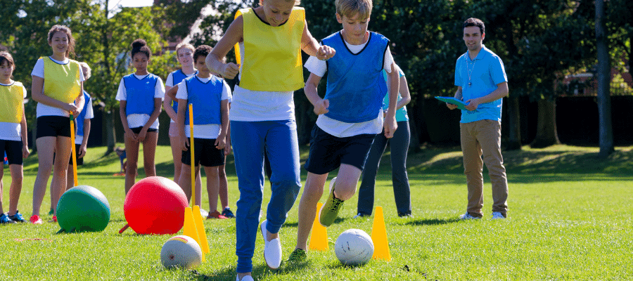 two teams kicking balls around obstacles.