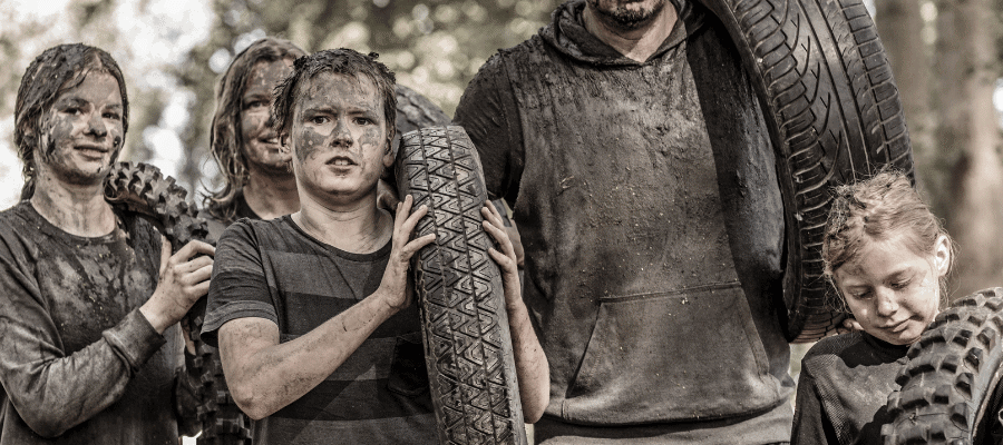 Family of five covered in mud carrying tires