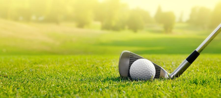 golf club hitting white golf ball on green lawn