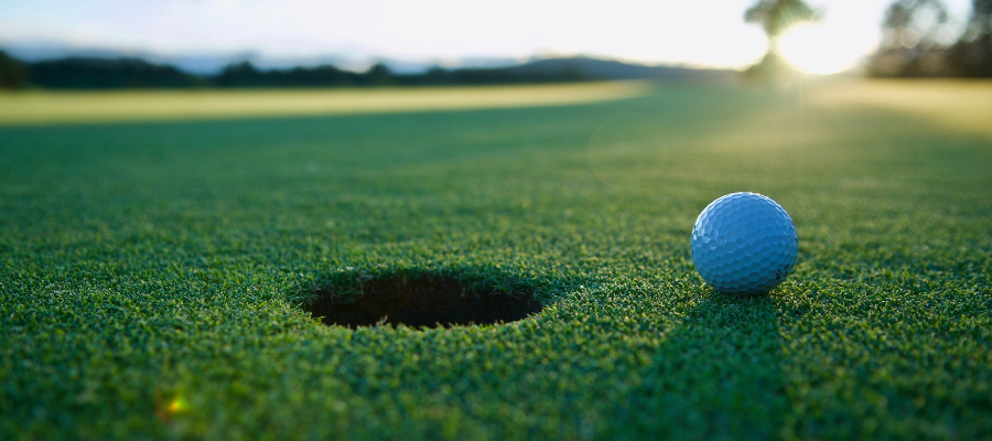 Golf ball about to enter hole