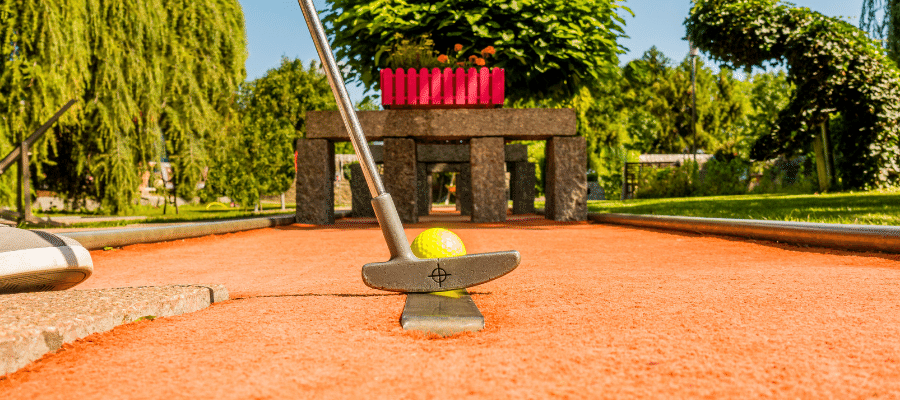Yellow golf ball about to be hit through tunnel of bricks on miniature golf course