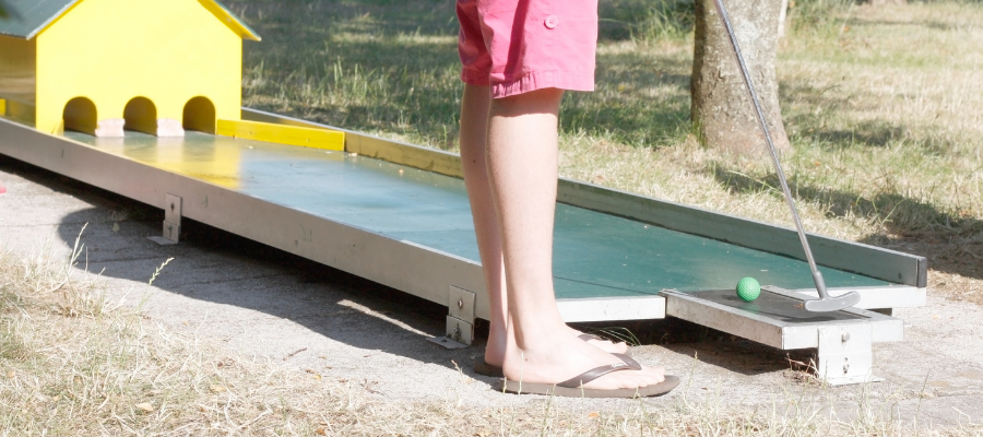 Person about to hit ball through miniature golf obstacle